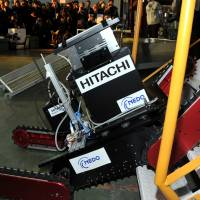 Stair master:  The  Tsubaki robot, developed by a startup firm of the Chiba Institute of  Technology and carrying a camera developed by Hitachi Ltd., climbs a set of stairs during a demonstration in Chiba Prefecture on Wednesday. | YOSHIAKI MIURA
