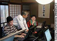 A student studying HTML interacts with his teacher at Nishijin Machiya Studio in Kyoto.