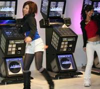 Dancers parade around KOnami's retro 'Jubeat' cabinet