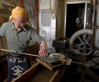 3rd-generation knife shop owner Masahisa Azuma sharpening a tuna knife in his shop. | TONY McNICOL PHOTO
