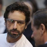 Half empty: Google cofounder Sergey Brin (left) wears the Google Glass device at an event in San Francisco on Feb. 20. | AP