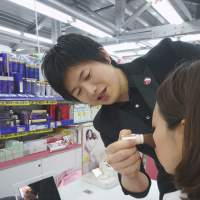 Makeup men: Kei Kishimoto applies makeup to a customer at a drugstore in the city of Osaka. | KYODO