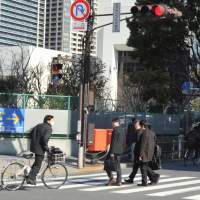 Failure to yield: A bicyclist ignores a red light at an intersection as pedestrians use a crosswalk Thursday in the Shibaura district in Minato Ward, Tokyo. | YOSHIAKI MIURA