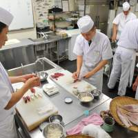 Best served raw: Students practice cutting fish and making sushi during a course at a sushi school hosted by the Sushi Zanmai restaurant chain in Tokyo last October. | AFP-JIJI