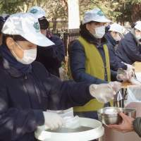 Hot meal: Volunteer workers belonging to the Japanese branch of the Taiwan-based Tzu Chi Foundation distribute food to homeless people in Yoyogi Park, Tokyo, on Jan. 7. | KYODO