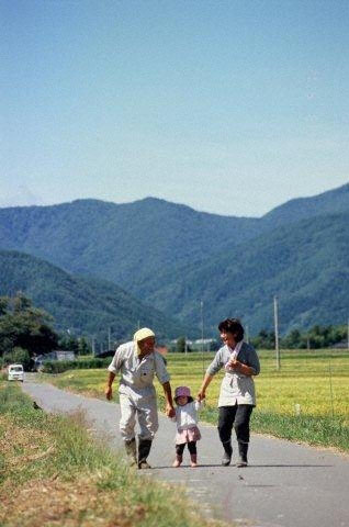 All is not calm: A scene from the documentary 'Fukushima, Rokkasho and Message to the Future' shows Kazuo Nakamura, a farmer in Koriyama, Fukushima Prefecture, walking with his wife and granddaughter on a road through rice paddies last October. | COURTESY OF KEI SHIMADA