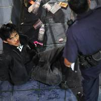 Red-handed: Police subdue Chad Ryan Desoto, 21, after he allegedly drove a Toyota Yaris into a crowd of people before slamming into an ABC Store and stabbing several tourists in the Tumon resort district Tuesday. | AP/KYODO
