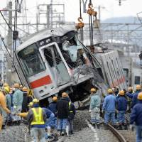 Unscheduled stop: Workers haul away a derailed Sanyo Electric Railway Co. train Wednesday in Takasago, Hyogo Prefecture. | KYODO
