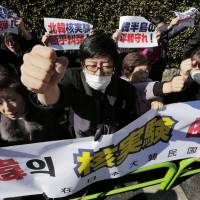 Nuclear reaction: South Korean residents of Japan hold a banner and raise their fists Wednesday during a Tokyo protest rally outside the General Association of Korean Residents to condemn North Korea's nuclear test the previous day. | AP