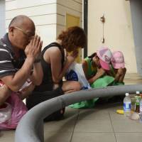 Mourning the loss: A family from Japan prays Thursday for the victims of a stabbing spree that took place Tuesday night in the Tumon tourist district on Guam. | KYODO