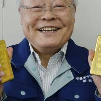Prize catch: Kunio Suno, the president of a fish market in Ishinomaki, Miyagi Prefecture, shows off a donated pair of gold bars worth ¥10 million Thursday. | KYODO