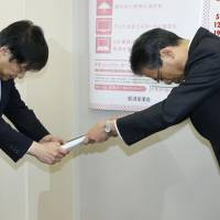 Standing on ceremony: Tohoku Electric Power Co. President Makoto Kaiwa (right) hands a rate hike application to Ichiro Takahara, chief of the Agency for Natural Resources and Energy, Thursday in Tokyo. | KYODO