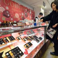Working up a sweet: A woman buys famed Belgian-brand Godiva chocolates at Tokyo's Takashimaya department store Wednesday, a day before Valentine's Day. | AFP-JIJI