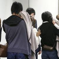 Grim homecoming: Relatives of two Japanese tourists killed in a stabbing rampage on Guam await the arrival of their bodies at Narita International Airport on Friday evening. | KYODO