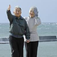 Royal promenade: Emperor Akihito and Empress Michiko take a walk on the seashore near the Imperial villa in Hayama, Kanagawa Prefecture, on Feb. 7. | KYODO
