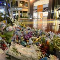 Outpouring of sympathy: Tourists on Guam pray Sunday in front of flowers and drinks placed on the ground where three Japanese were slain and several others were wounded in a rampage on Feb. 12. | KYODO