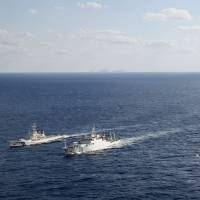 Cat and mouse: A Japan Coast Guard patrol ship (far left) tries to chase off a Chinese maritime surveillance vessel (second from left) that entered Japan's territorial waters near the islet of Uotsuri in the Senkaku chain Oct. 2. | KYODO