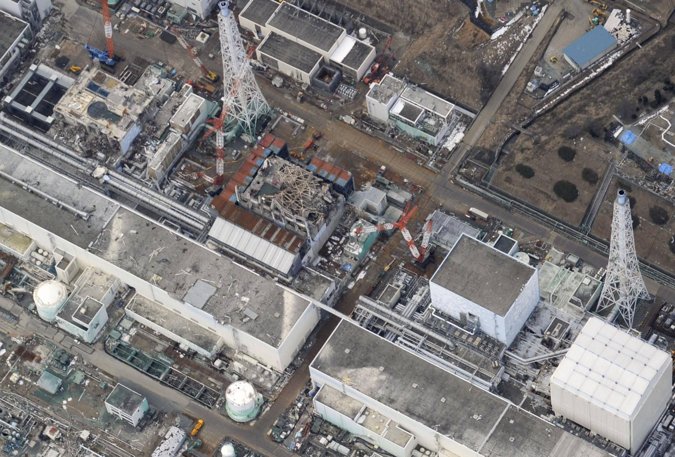 An aerial photo taken on Feb. 10 shows from left the reactors 1 to 4 at Fukushima No.1 power plant. The International Atomic Energy Agency plans to propose a multinational mission to decommission the wrecked reactors. | KYODO