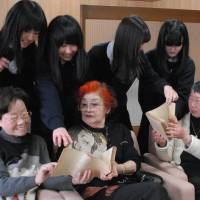 Sumiko Horii (front left), Hiroko Inoue (front center) and Yuriko Tokuda explain about the 'washi' paper used to make balloon bombs with students of Sugiyama Girls' High School's broadcasting club at the school Sunday. | THE CHUNICHI SHIMUBUN