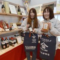 Tohoku pride: Akie Hoshi (right) and Aki Murakami showcase products of the soy sauce and miso maker they work for in Rikuzentakata, Iwate Prefecture, on Jan. 31. | KYODO