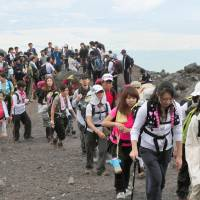 Freeloaders?: A horde of visitors trudges up Mount Fuji last August. The local governments of Yamanashi and Shizuoka may start charging an admission fee to climb Japan's highest peak, to raise funds for the preservation of its environment. | KYODO