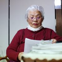 Fine print: Itoko Uchida, 82, reads a document in her Fujimi, Saitama Prefecture, home on Feb. 19. | BLOOMBERG