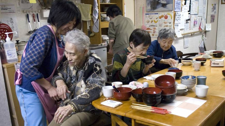 Aiding mobility: Kimi Ouchi, 85, is helped to her feet by an employee as two other seniors eat dinner at a privately run home for the elderly in Yubari, Hokkaido, in March 2007.