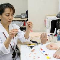 Whole again: Yukako Fukushima, a maker of prosthetics, paints an artificial pinkie in her office in the city of Osaka on Feb. 1. | KYODO