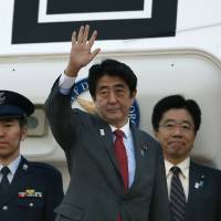 Gear up: Prime Minister Shinzo Abe waves at Tokyo's Haneda airport Thursday as he departs for Washington.  | AP