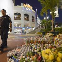 All quiet: A policeman Wednesday night passes a makeshift shrine of flowers and drinks left in memory of victims of a man's deadly Feb. 12 rampage in Guam's Tumon tourist district.  | KYODO