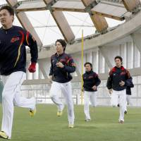 Catch me if you can: Pitcher Masahiro Tanaka (left) leads his Samurai Japan teammates during an exercise at the team's Miyazaki training camp on Monday. | KYODO