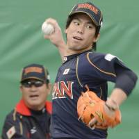 I've got my eye on you: Carp ace Kenta Maeda pitches as former Hiroshima great and current Japan manager Koji Yamamoto watches on Thursday in Miyazaki. | KYODO