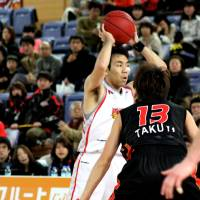 Surveying his options: Veteran guard Masahiro Oguchi of the Hamamatsu Higashimikawa Phoenix looks to pass as Osaka Evessa guard Takuya Hashimoto defends him during Sunday's bj-league game in Osaka. | HIROAKI HAYASHI