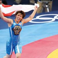 Saori Yoshida celebrates at the London 2012 Olympic Games after defeating Canada's Tonya Lynn Verbeek in the Women's 55kg Freestyle gold medal match. | AFP-Jiji