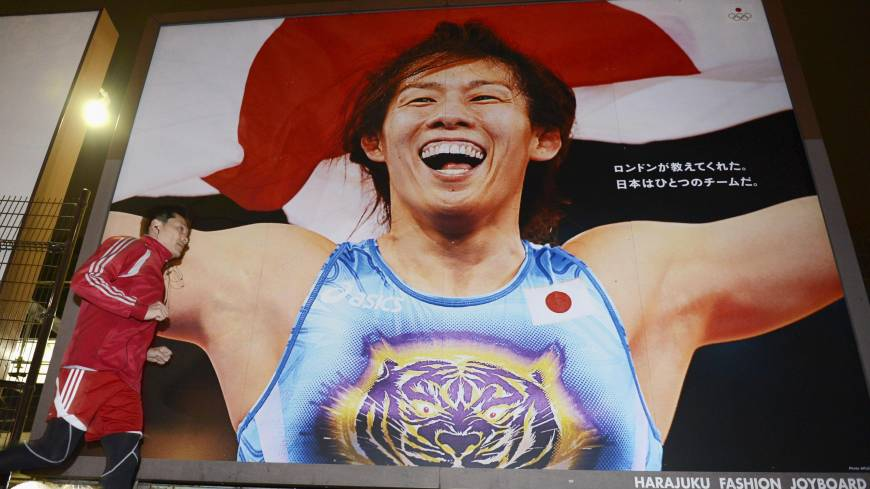 Endangered species: A man runs past a billboard featuring three-time Olympic gold medal-winning wrestler Saori  Yoshida in  Tokyo on  Tuesday. The IOC's executive board voted the same day to cut wrestling from the 2020 Games.