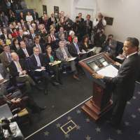Shutter bug: President Barack Obama and reporters smile as he reacts to a noise coming from a camera in the James Brady Press Briefing Room at the  White House in  Washington on  Tuesday. | AP