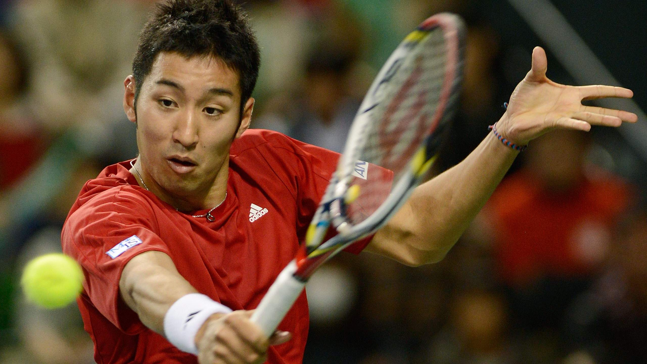 Debut delight: Yasutaka Uchiyama plays a shot during his singles match in Japan's 5-0 Davis Cup win over Indonesia on Sunday.  | AFP-JIJI