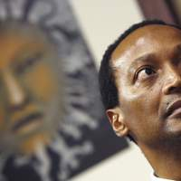 Giving it away: South African businessman and outgoing Business Unity South Africa President Patrice Motsepe looks listens to the newly appointed chief of BUSA, Brian Molefe, speak on May 7, 2008, at BUSA's headquarters in Sandton, South Africa. | AFP-JIJI