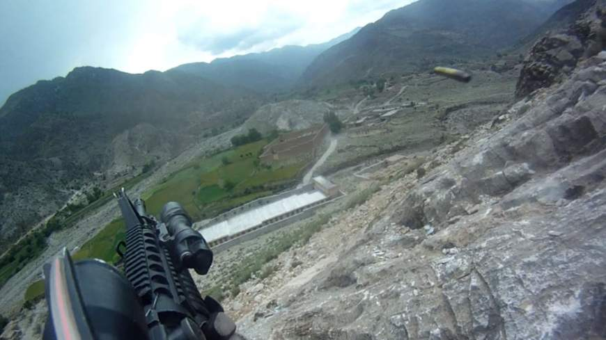 Not a video game: This screen grab from video captured by army Pfc. Ted Daniels' helmet camera shows a shell casing being discharged from his weapon as he returns fire during an April 2012 firefight on a hillside in Afghanistan.