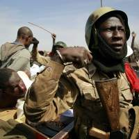 Militant behavior: Malian soldiers guard suspected Islamist extremists in the northern city of Gao on Jan. 29. | AP