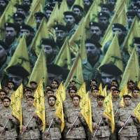 Party line: Hezbollah fighters hold their party's flags during a rally in Beirut in 2008. Lebanon's prime minister expressed his readiness  Tuesday to cooperate with Bulgarian authorities over a bomb attack linked to the group that killed five Israelis. | AP