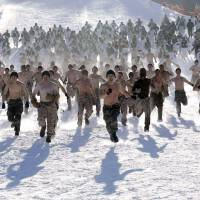 Cold war: Shirtless South Korean Marines and their U.S. counterparts run on a snow-covered slope during a joint winter military exercise in Pyeongchang, east of Seoul, on Thursday. More than 400 marines from the two countries are participating in the exercise, which began Monday and ends Feb. 22. | AP