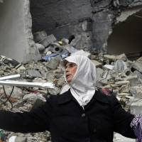 Gone: A woman stands amid the ruins of her house in Aleppo, Syria, on  Thursday after it was destroyed by government warplanes. Eleven members of her family were killed. | AP