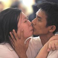 Lip-smacking good: Laksana  Tiranarat (left) and Ekkachai kiss in Pattaya on  Thursday. | AFP-JIJI