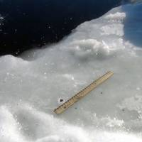 Space odyssey: A small dark object is shown embedded in the ice next to a ruler at the edge of a hole in the ice of a lake where a meteor apparently fell last Friday outside the town of Chebakul in Russia's Chelyabinsk region. | AFP-JIJI