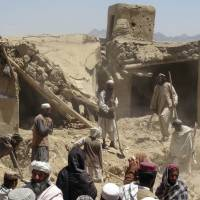 Death from above: Afghan villagers gather near a house destroyed in an apparent drone strike in Logar Province on June 6. | AP