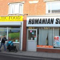Something for everyone: A couple walk past shops catering to Eastern Europeans in Boston, England, on Tuesday. | AFP-JIJI