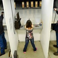 Aiming high: Two men and a girl take part in a shooting competition at the Red River Regional Marksmanship Center on Tuesday in West Fargo, North Dakota — one of the gun-friendliest states in the U.S. | THE WASHINGTON POST