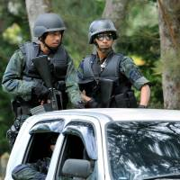 Making a claim: Police from Malaysia's General Operations Force patrol Tuesday in the town of Lahad Datu in Sabah state. In a shootout Friday between security forces and followers of Sultan Jamalul Kiram III, 14 people were killed. | AP