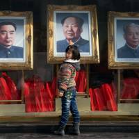 Historical figures: A girl stands before portraits of former Chinese leaders Zhou Enlai, Mao Zedong and Liu Shaoqi in Beijing at the end of February, ahead of a key parliamentary meeting of China's top leaders in the capital this week. | AFP-JIJI